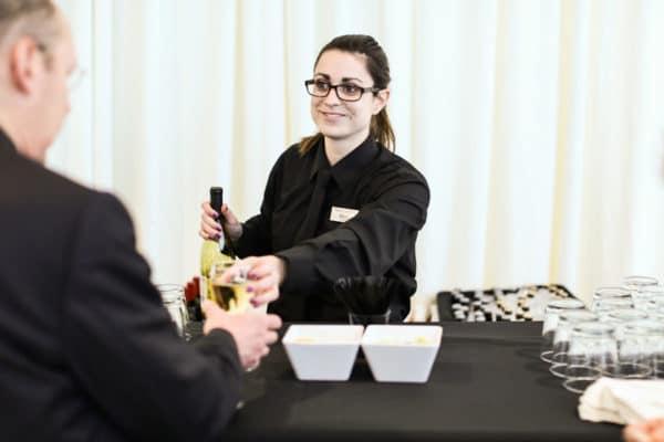 Emily, nuphoriq's graphic designer, bartending an event